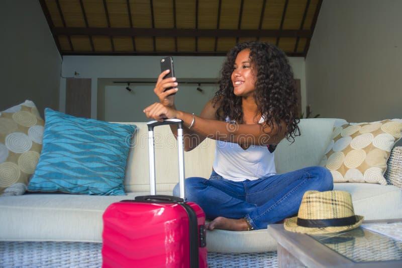 Młoda atrakcyjna i szczęśliwa czarna latyno-amerykański kobieta z walizki obsiadaniem na kanapy leżance opuszcza dla wakacji w do zdjęcie stock
