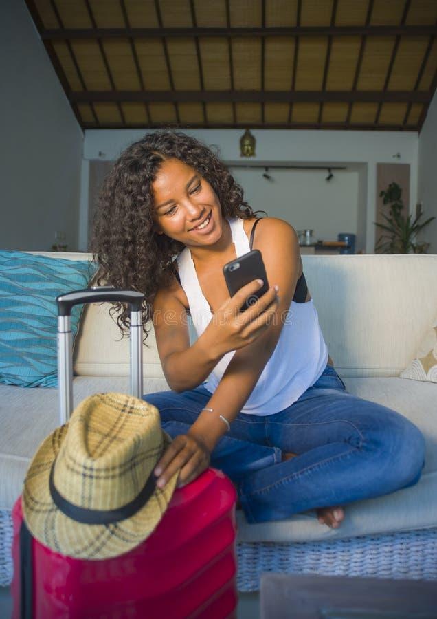 Młoda atrakcyjna i szczęśliwa czarna latyno-amerykański kobieta z walizki obsiadaniem na kanapy leżance opuszcza dla wakacji w do obraz stock
