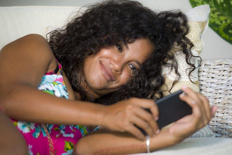 Młoda atrakcyjna i szczęśliwa czarna latynoska kobieta z walizki obsiadaniem na kanapy leżance opuszcza dla wakacji w domu potyka obrazy royalty free