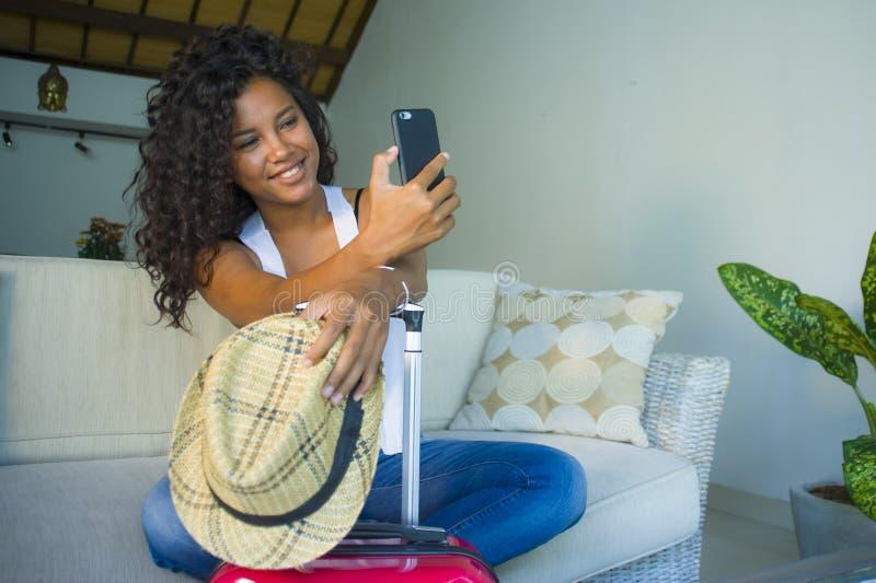 Młoda atrakcyjna i szczęśliwa czarna latynoska kobieta z walizki obsiadaniem na kanapy leżance opuszcza dla wakacji w domu potyka obraz royalty free