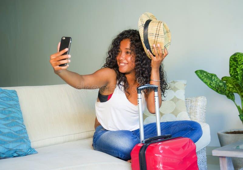 Młoda atrakcyjna i szczęśliwa czarna latynoska kobieta z walizki obsiadaniem na kanapy leżance opuszcza dla wakacji w domu potyka zdjęcia royalty free