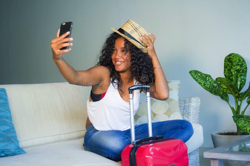 Młoda atrakcyjna i szczęśliwa czarna latynoska kobieta z walizki obsiadaniem na kanapy leżance opuszcza dla wakacji w domu potyka obrazy stock