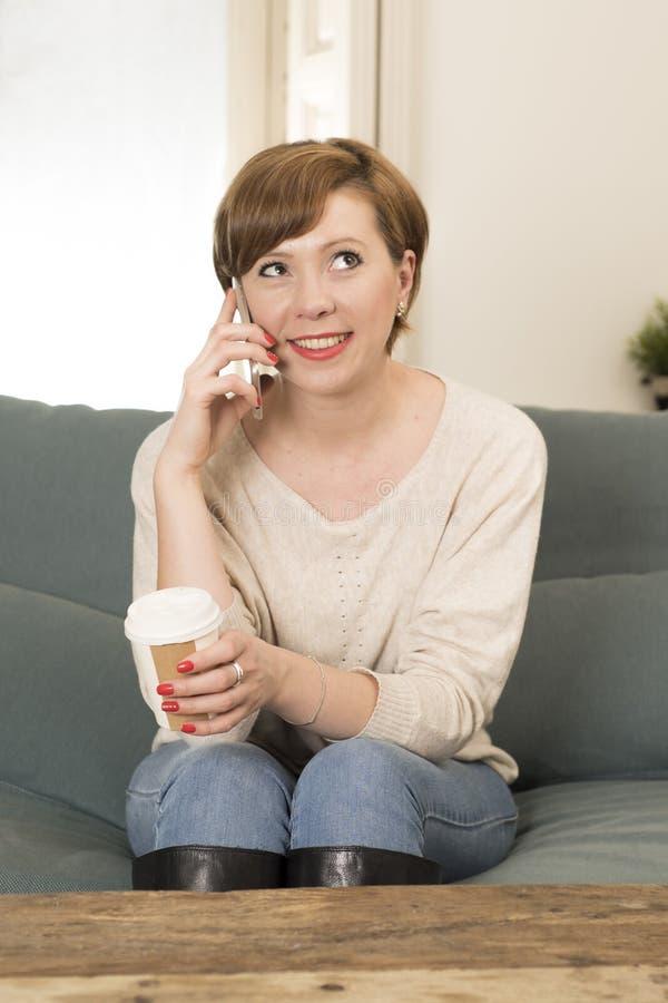 Młoda atrakcyjna i szczęśliwa czerwona włosiana kobieta siedzi kanapy leżankę pije kawę opowiada na telefonie komórkowym w domu r fotografia stock