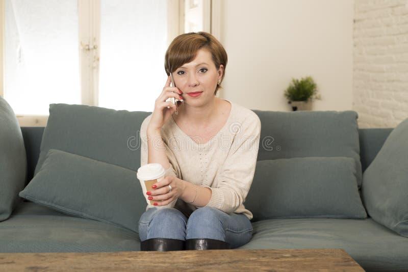 Młoda atrakcyjna i szczęśliwa czerwona włosiana kobieta siedzi kanapy leżankę pije kawę opowiada na telefonie komórkowym w domu r obraz royalty free