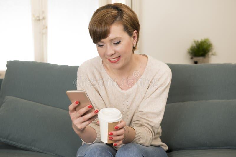 Młoda atrakcyjna i szczęśliwa czerwona włosiana kobieta siedzi w domu kanapę c obraz royalty free