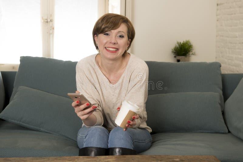 Młoda atrakcyjna i szczęśliwa czerwona włosiana kobieta siedzi w domu kanapę c zdjęcie stock