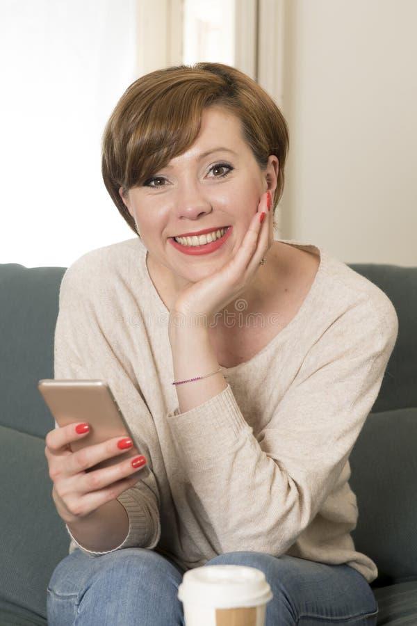 Młoda atrakcyjna i szczęśliwa czerwona włosiana kobieta siedzi w domu kanapę c obrazy royalty free