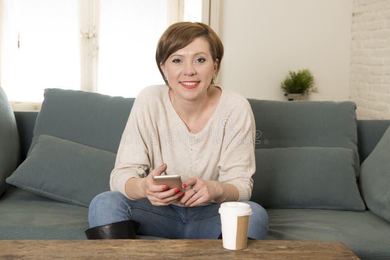 Młoda atrakcyjna i szczęśliwa czerwona włosiana kobieta siedzi w domu kanapę c obrazy stock