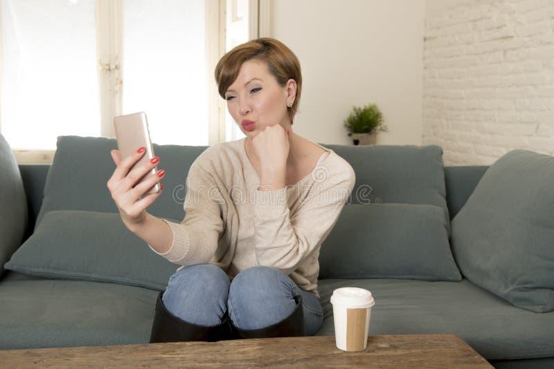 młoda atrakcyjna i szczęśliwa czerwona włosiana kobieta siedzi w domu kanapy leżankę pije kawę bierze selfie obrazek z telefonem  obraz royalty free