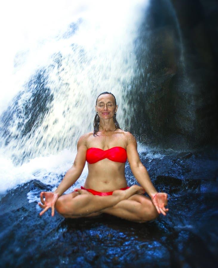 Młoda atrakcyjna i szczęśliwa kobieta z dysponowanego ciała joga raju siklawy strumienia ćwiczy mokrym poniższym tropikalnym obsi zdjęcia royalty free