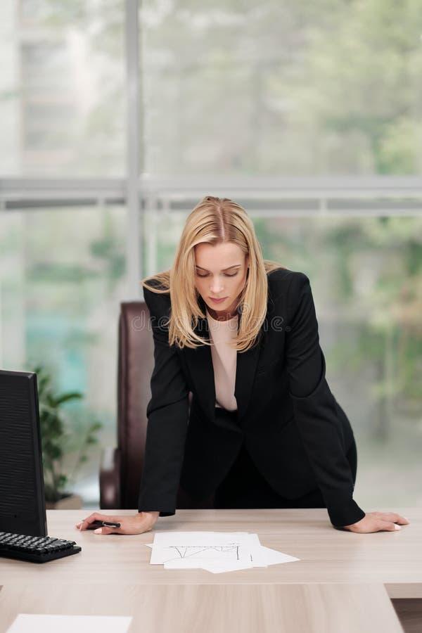 Młoda atrakcyjna Kaukaska blond kobieta w czarnym garniturze siedzi przy biurkiem w jaskrawym biurze Studiować papierowych dokume fotografia royalty free
