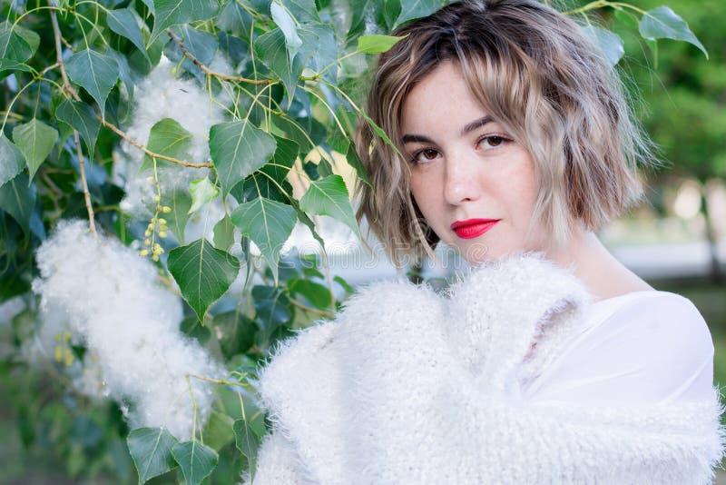 Młoda atrakcyjna kobieta chodzi pozować w parku z czerwonymi wargami w białych przypadkowych ubraniach obrazy royalty free