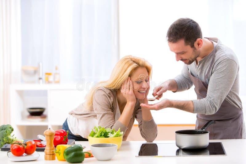 Młoda atrakcyjna kobieta daje jedzeniu jej mąż smak zdjęcia stock
