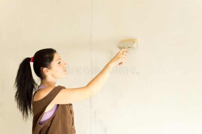 Młoda atrakcyjna kobieta dekoruje ściany fotografia stock
