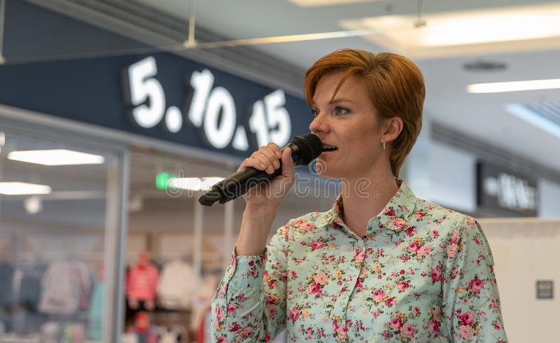 Młoda atrakcyjna kobieta mityguje ogólnospołecznego wydarzenie w biznesowym domu dla społeczeństwa zdjęcia stock