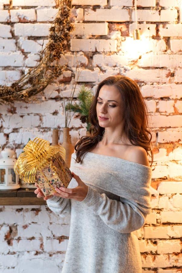 Młoda atrakcyjna kobieta pokojowo egzamininuje prezent w wygodnym pulowerze w rocznika pokoju zdjęcie royalty free