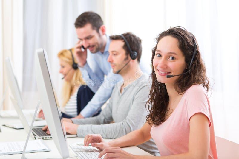Młoda atrakcyjna kobieta pracuje w centrum telefonicznym obrazy stock