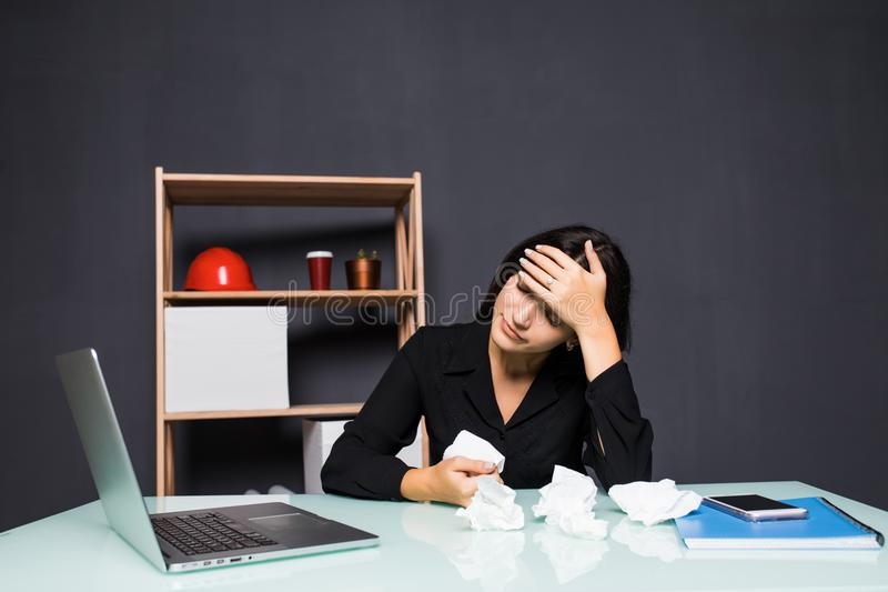 Młoda atrakcyjna kobieta przy nowożytnym biurowym biurkiem, pracujący na laptopie, masuje świątynie zapominać o stałych migrenach fotografia stock