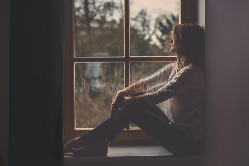 Młoda atrakcyjna kobieta, siedzi na nadokiennym, przyglądającym outside, obraz royalty free