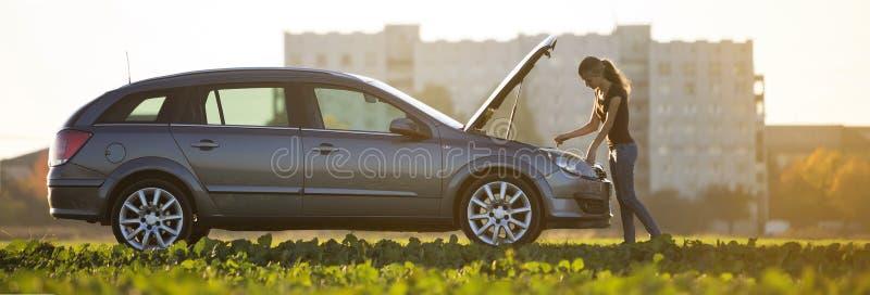 Młoda atrakcyjna kobieta sprawdza nafcianego poziom w silniku samochód z strzelającym kapiszonem używać dipstick na jasnym niebo  obrazy royalty free