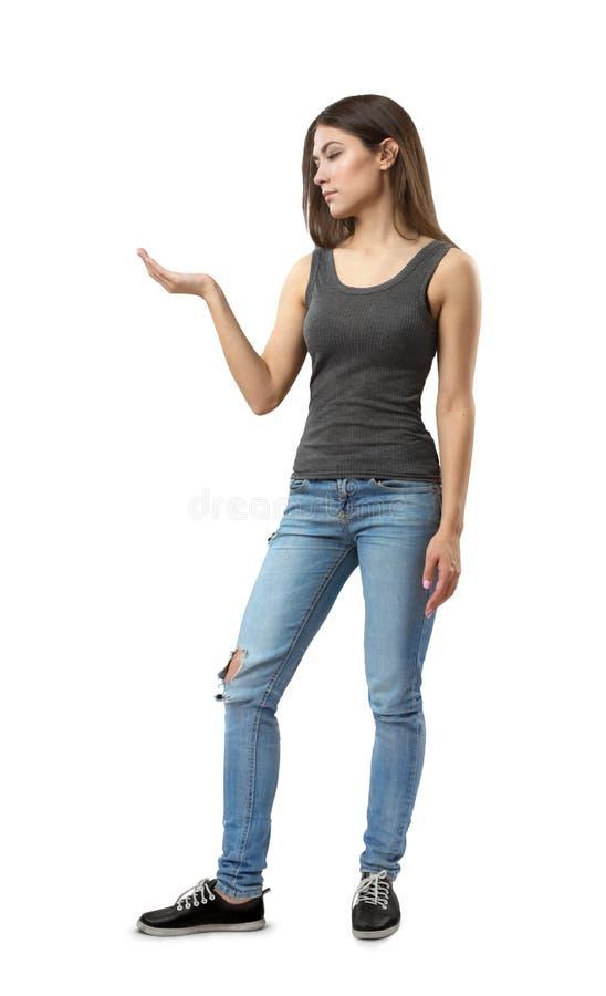 Młoda atrakcyjna kobieta stoi w półzwrocie z prawym ramieniem w szarym sleeveless wierzchołku i niebieskich dżinsach zginał przy  obraz royalty free
