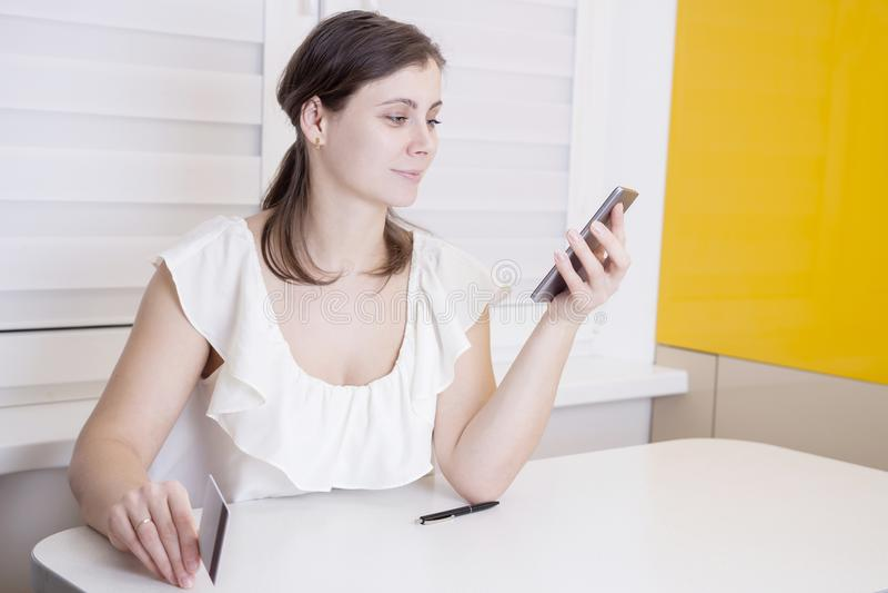 Młoda atrakcyjna kobieta używa nowożytnego smartphone i chwyty w ręki plastikowej kredytowej karcie Online zapłata obrazy stock