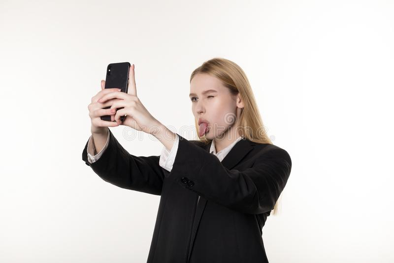 Młoda atrakcyjna kobieta w ciemnym kostiumu bierze fotografie, zamyka jeden oko używać telefon komórkowego, i pokazywać jęzor obraz royalty free