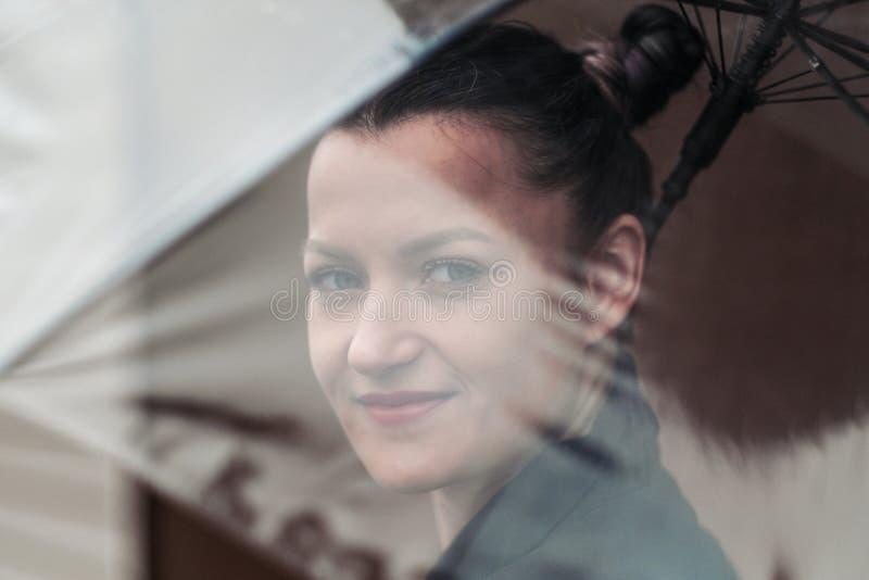 Młoda atrakcyjna kobieta w czarny kurtki i niebieskich dżinsów pozować plenerowy przeciw tłu budynek obraz stock