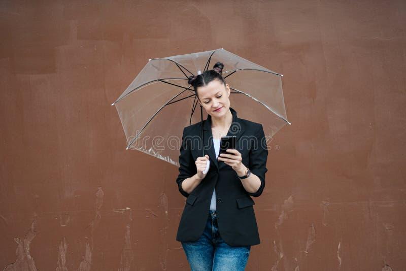 Młoda atrakcyjna kobieta w czarny kurtki i niebieskich dżinsów pozować plenerowy przeciw tłu budynek zdjęcia stock