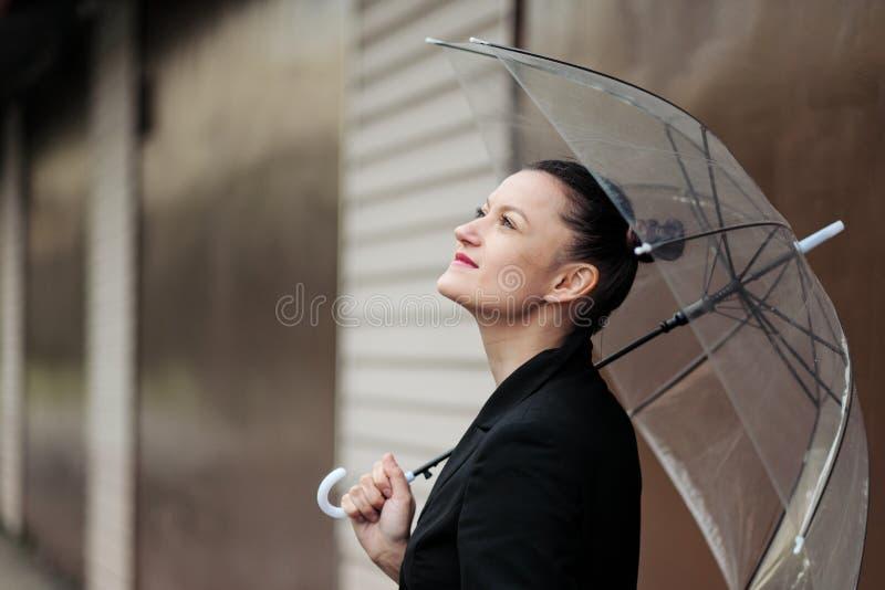 Młoda atrakcyjna kobieta w czarny kurtki i niebieskich dżinsów pozować plenerowy przeciw tłu budynek zdjęcie stock