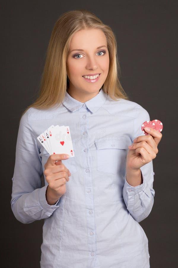 Młoda atrakcyjna kobieta z cztery grzebaków układami scalonymi nad popielatym i as fotografia stock