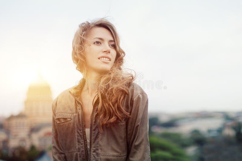 Młoda atrakcyjna kobieta z dobrym nastrojem cieszy się pięknego miasto krajobraz podczas gdy stojący na dachu budynek, powabny uś zdjęcia royalty free