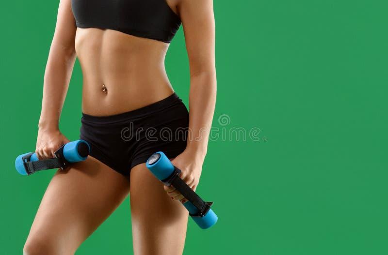 Młoda atrakcyjna kobieta z dumbbells w jej rękach pozuje w stu fotografia stock
