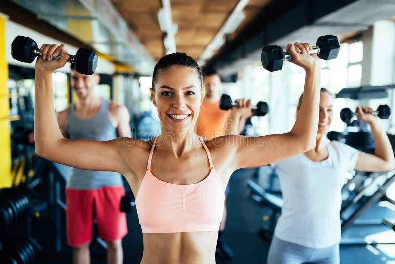 Młoda atrakcyjna kobieta z robić ćwiczy z przyjaciółmi w gym zdjęcie royalty free