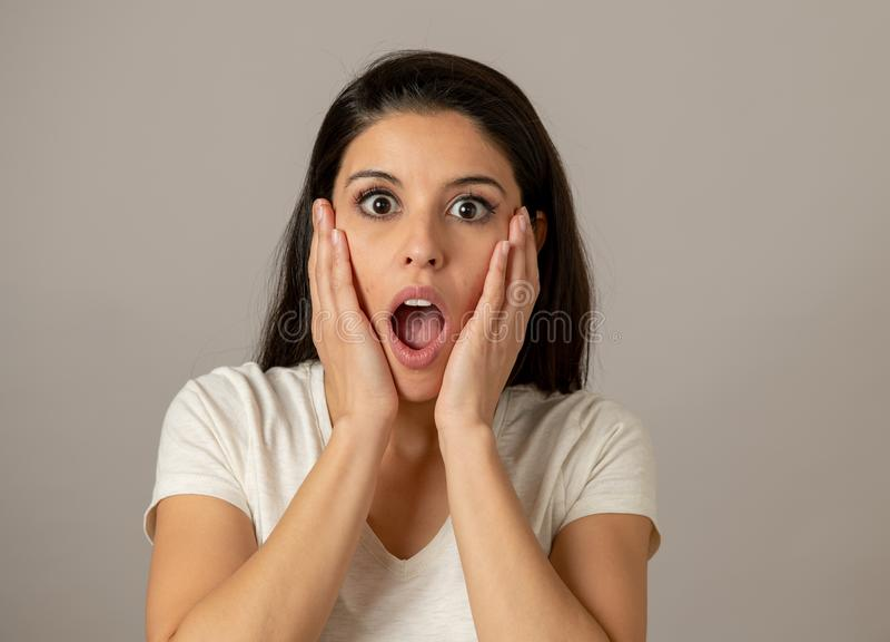 Młoda atrakcyjna kobieta z twarzą, oczami i usta szeroko otwarty zdziwionymi i szokującymi, zdjęcie stock