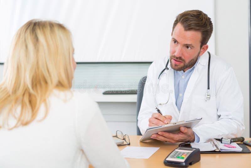 Młoda atrakcyjna lekarka bierze notatki podczas gdy pacjent mówi obrazy stock