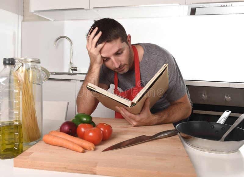 Młoda atrakcyjna mężczyzna przepisu kuchenna czytelnicza książka w stresie w domu obrazy royalty free