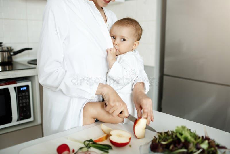 Młoda atrakcyjna matka breastfeeding jej nowonarodzonego ślicznego syna na kuchennym stole podczas gdy gotujący zdrowego śniadani obraz royalty free
