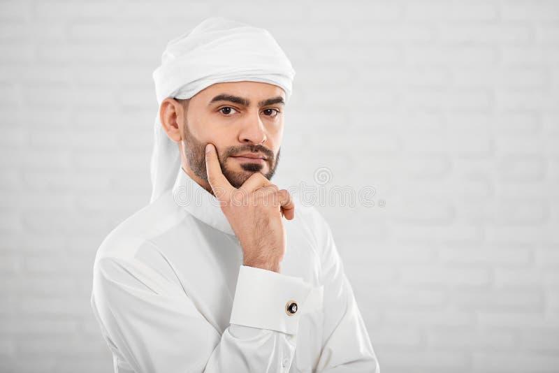 Młoda atrakcyjna muzułmańska samiec w tradycyjny Islamski cloting myśleć o coś zdjęcia stock