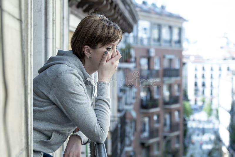 Młoda atrakcyjna nieszczęśliwa przygnębiona osamotniona kobieta płacze patrzeć w stresie na balkonie w domu zdjęcia royalty free