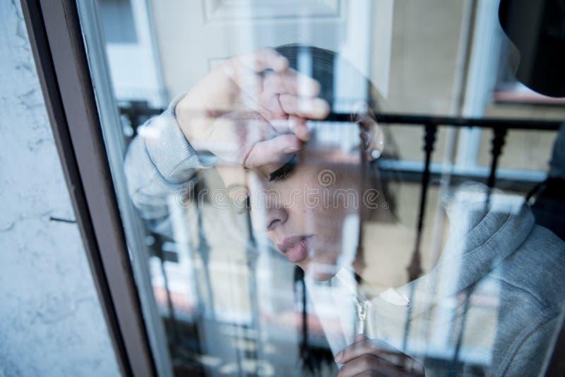 Młoda atrakcyjna nieszczęśliwa przygnębiona osamotniona kobieta patrzeje beznadziejny opierać na okno w domu zdjęcia royalty free