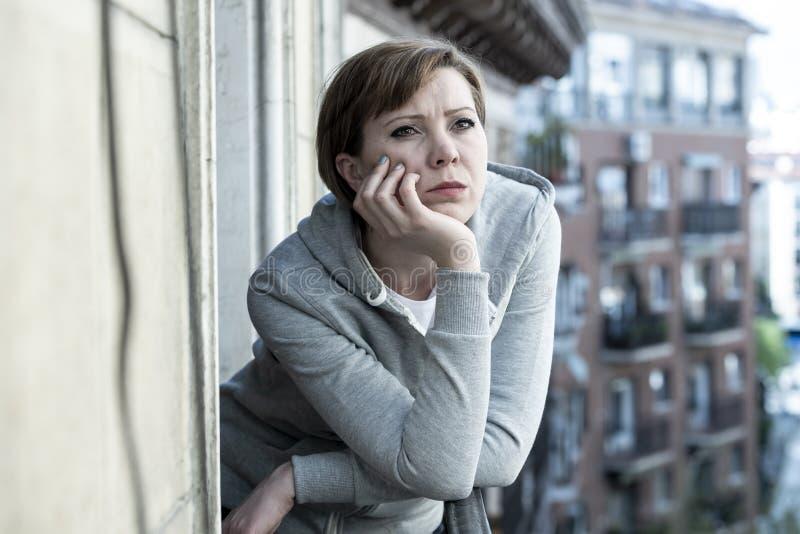 Młoda atrakcyjna nieszczęśliwa przygnębiona osamotniona kobieta patrzeje smutny na balkonie w domu Miastowy widok zdjęcia stock
