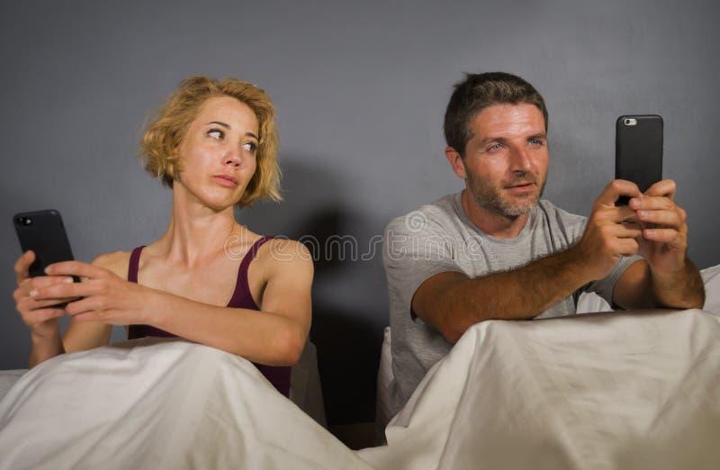 Młoda atrakcyjna para używa telefon komórkowego w łóżku ignoruje each innego prześladującego networking w interneta nałogu i zani fotografia royalty free
