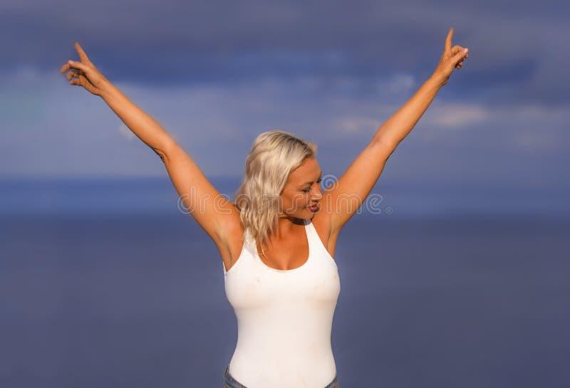 Młoda atrakcyjna, piękna 30s blondynu kobieta w i zwiera podesłanie ręki szczęśliwe i rozochoconego pozować zdjęcia royalty free