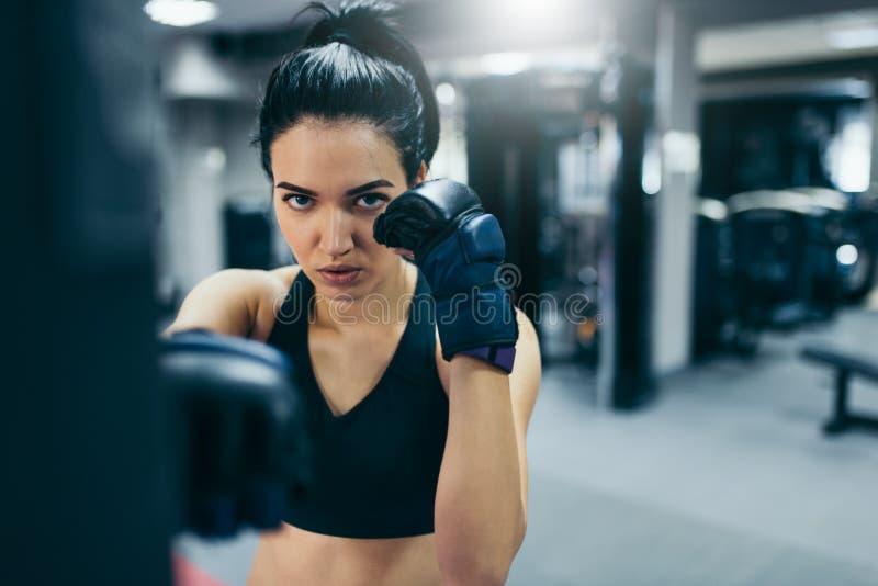 Młoda atrakcyjna powozowa kobieta uderza pięścią torbę z kickboxing rękawiczkami trenuje w gym treningu Sport, sprawność fizyczna fotografia royalty free