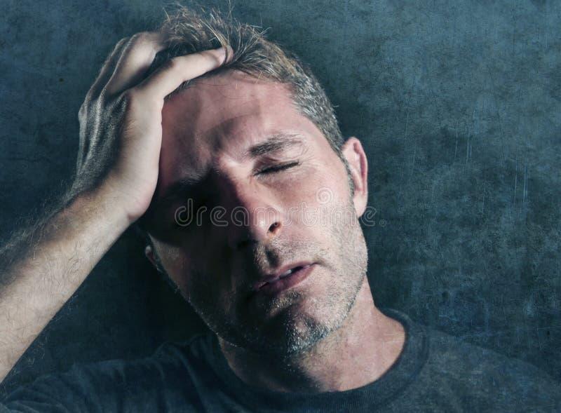 Młoda atrakcyjna, smutna mężczyzna cierpienia depresja i migrena z ręką na jego tempo głowie patrzeje martwiącego się i choroby i obraz stock