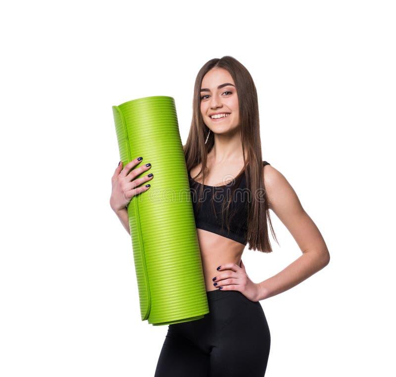 Młoda atrakcyjna sprawności fizycznej kobieta przygotowywająca dla treningu mienia zieleni joga maty odizolowywającej na białym t obraz stock