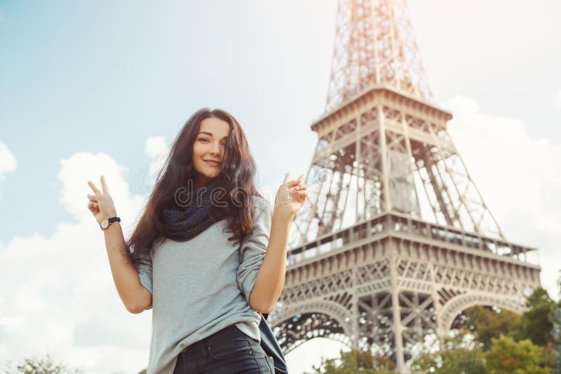 Młoda atrakcyjna szczęśliwa kobieta pokazuje pokoju gesta wieżę eiflą w Paryż, Francja fotografia stock