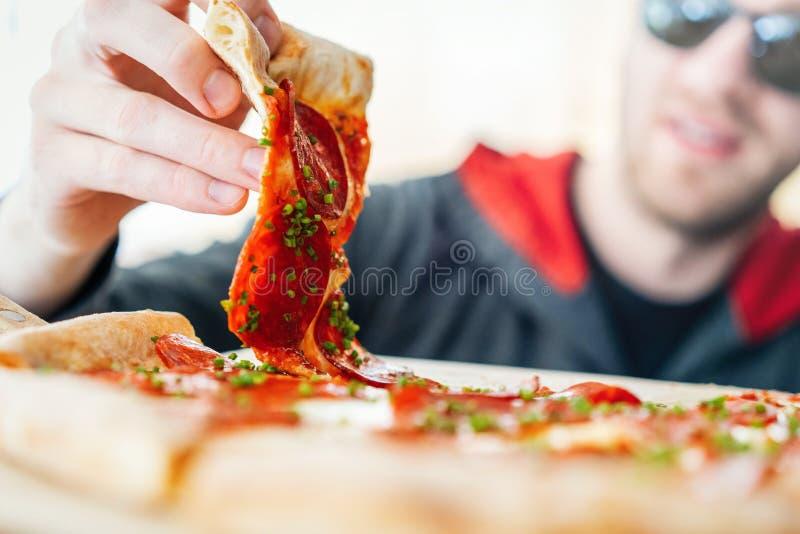 Młoda atrakcyjna uśmiechnięta mężczyzny łasowania pizza przy uliczną kawiarnią Nabranie posi?ek Nabranie dzień obraz stock