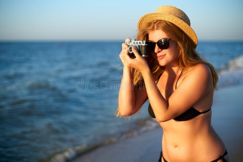 Młoda autentyczna kobieta z rocznik retro ekranową kamerą cieszy się tropikalną plażę na wakacje Żeńska podróż zdjęcie royalty free